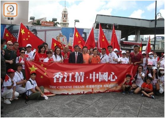 """何君尧与香港市民团体在尖沙咀五支旗杆参加升旗仪式。(图源:香港""""东网"""")"""