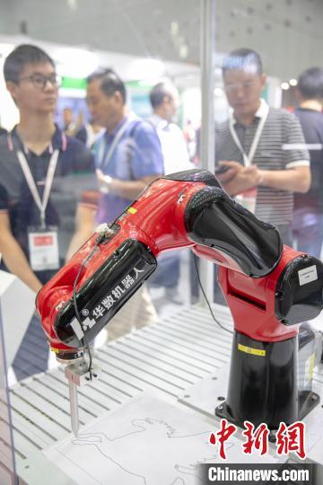 """在第五届中国(广东)国际""""互联网 """"博览会展出的绘画机器人(资料图)。 龙翔 摄"""