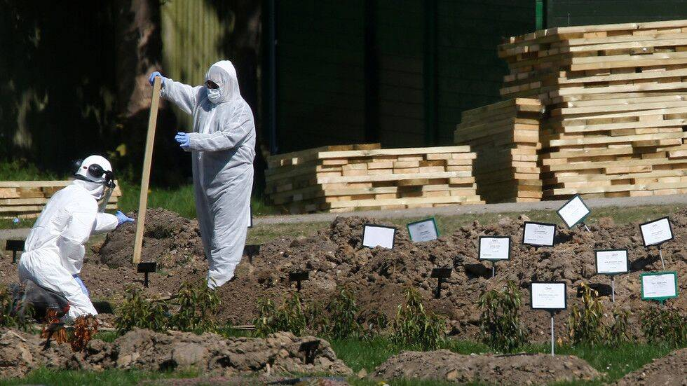 疫情期间,工人身穿防护服制作坟墓。图源:路透社
