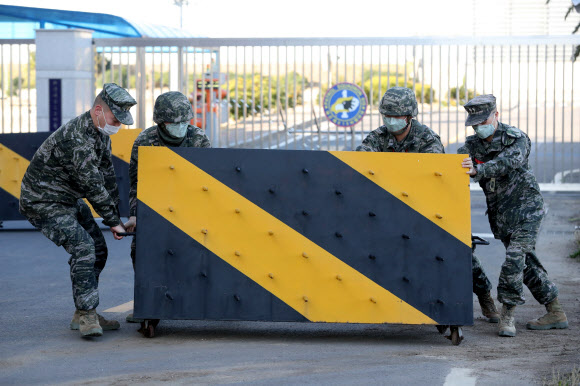 韩国某部队正门前,官兵们设置路障防疫(韩联社)