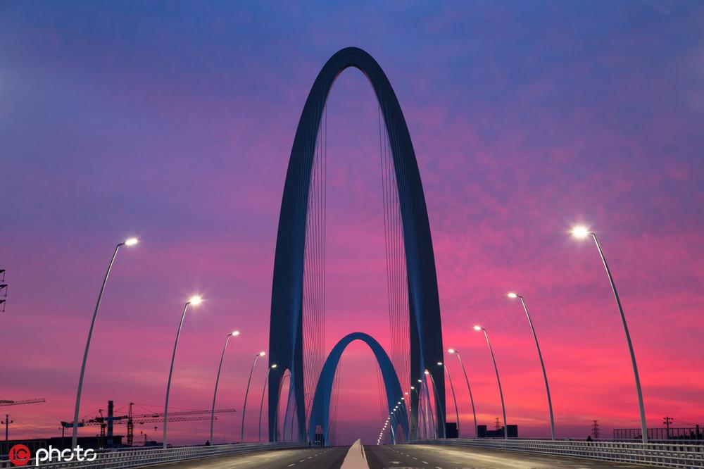 北京新首钢大桥朝霞绚烂多彩吸引市民驻足观看